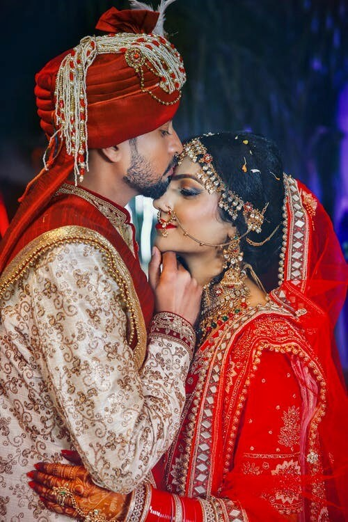 Traditional Indian Red and Gold Wedding Attires for Bride and Groom, Symbol of Love and Abundance