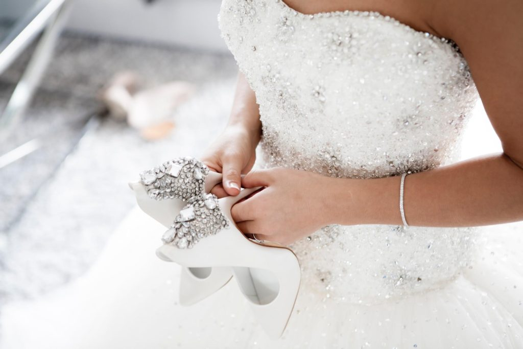 Bride holds wedding shoes