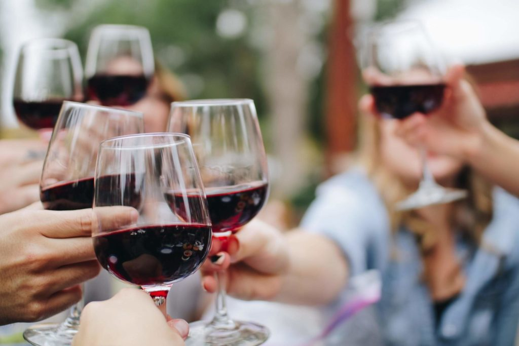 Group of people cheering with glasses of red wine