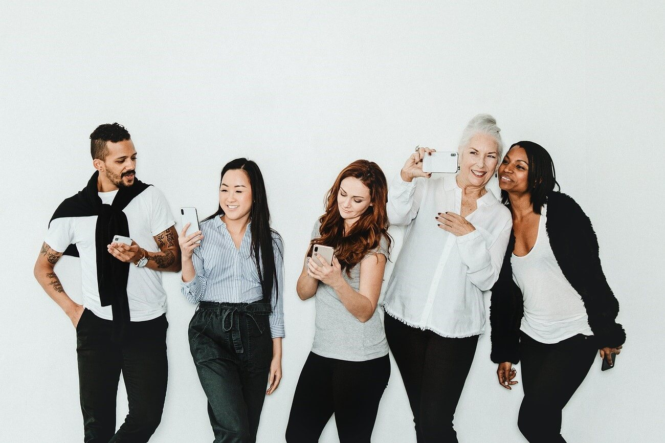 Group of people holding a phone to take a selfie