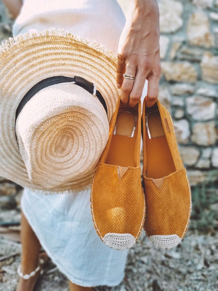 Woman holding straw hat and espadrilles