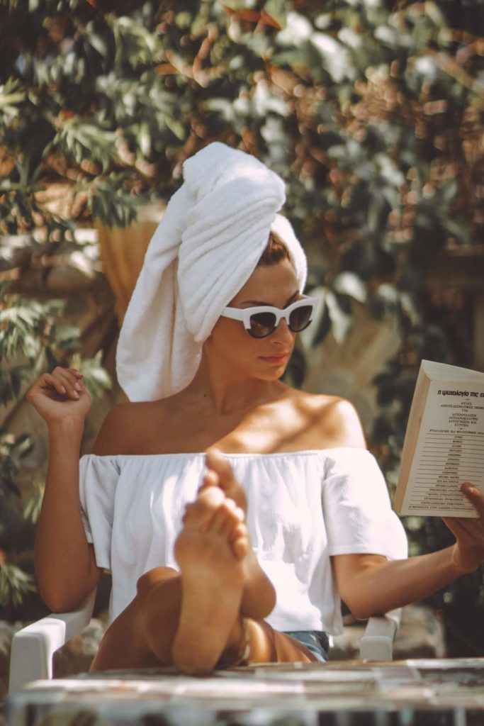 Women with white sunglasses by the pool.