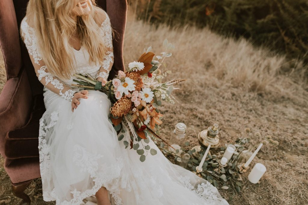 Woman in a wedding dress with her bouquet sitting on the grass