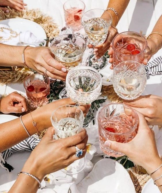 Girls holding their drinks at the bridal shower, making a toast