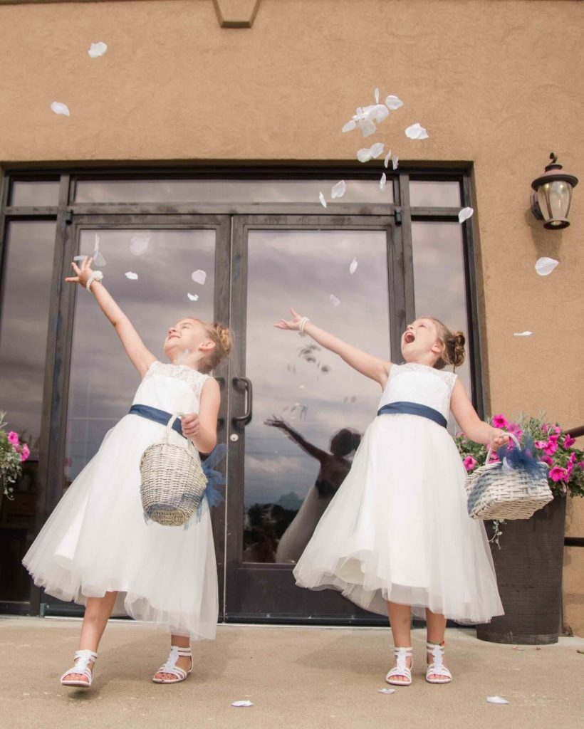 Two junior bridesmaids throwing white flower petals