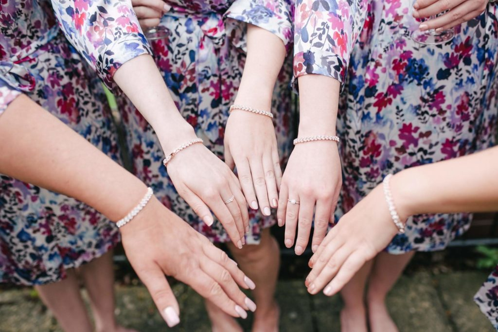 Bridesmaids and the bride showing off their matching bracelets