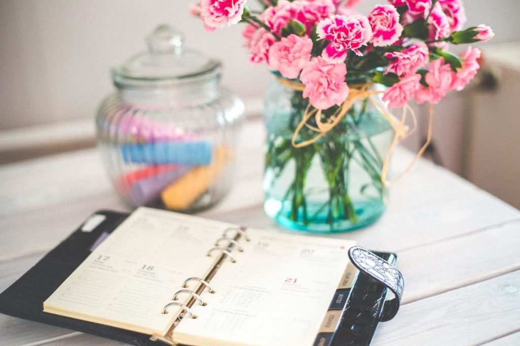 Planner, a vase with flowers, and a candy jar on the white table